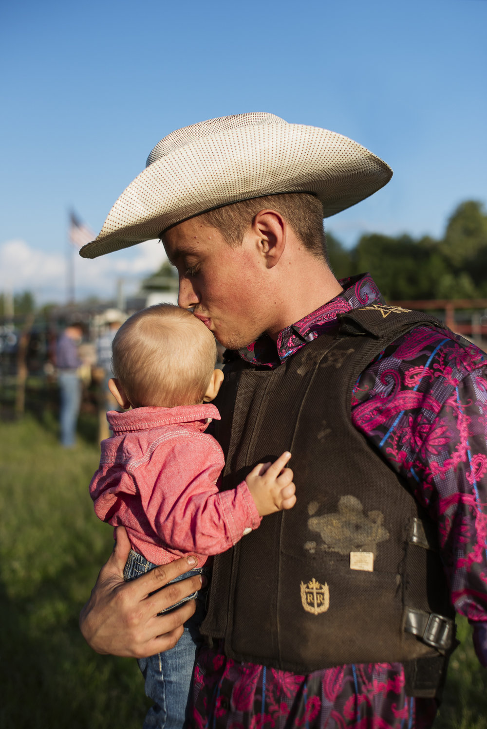 Jack Sorokin Rodeo Portrait Young Man Kissing Baby Head Sunset North Carolina Photography Editorial Madison County Marshall