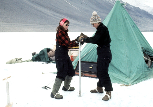 Terry Tickhill (light hat) and Eileen McSaveney (red headband) use a hand augur to drill Lake Vanda, Wright Valley, Antarctica, during the 1969-1970 field season. Water collected during this effort was used to date the lake. Courtesy: National Science Foundation