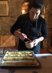 Margareta brushes the cantuccini with beaten egg.