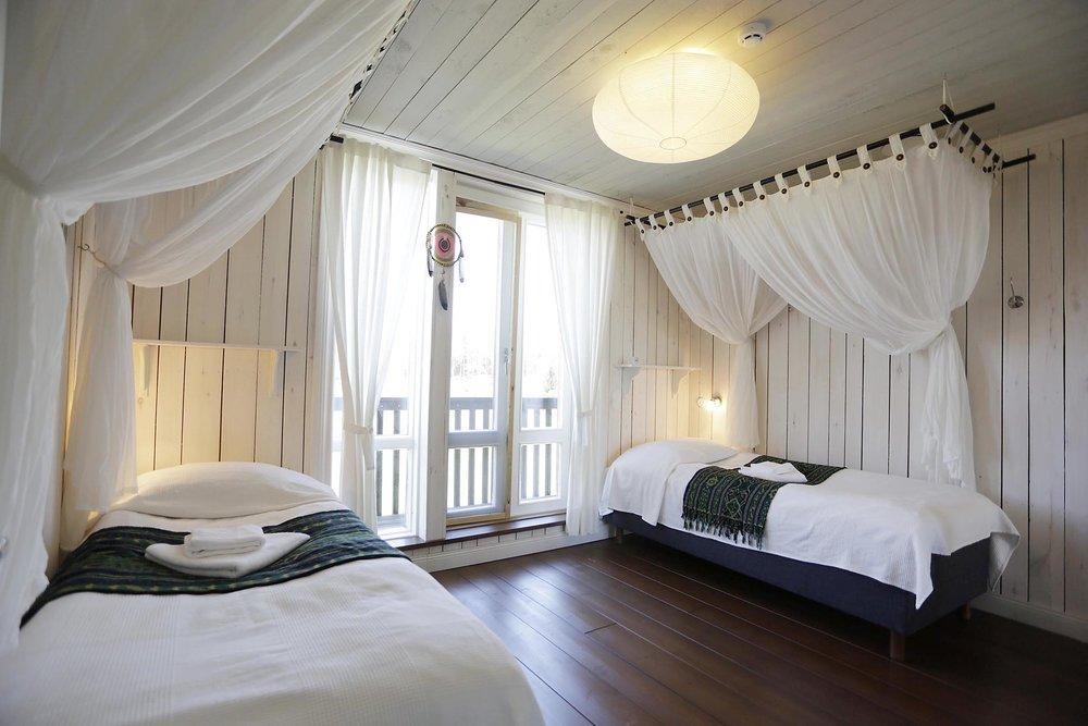 Huone 4: oma tilava kylppäri ja vessa, kaksi sänkyä, parveke ja 2. kerroksen näköala pellon yli.