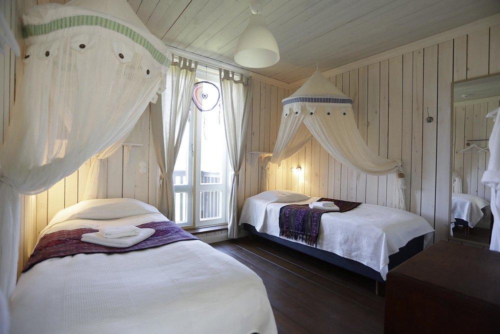 Huone 5: oma tilava kylppäri ja vessa, kaksi sänkyä, parveke ja 2. kerroksen näköala pellon yli.