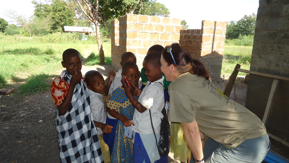 Vicki is seen here taking a break from the dispensary to show some local children their pictures.