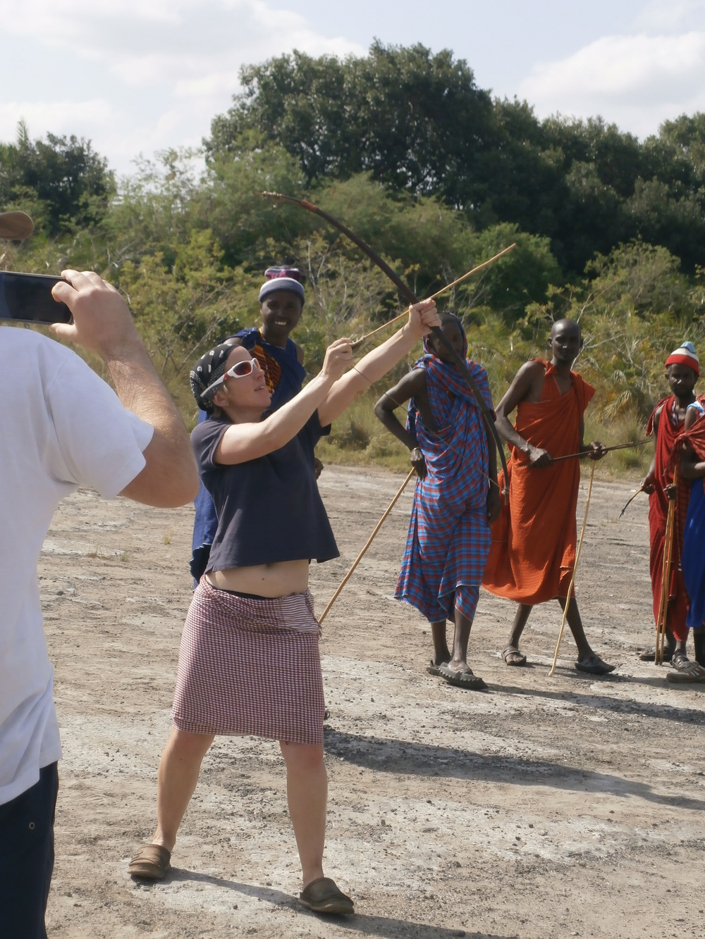 The maasai gaze in amazement to see a women competing in their very traditional use of the Bow and Arrow.  This weapon is still used by the maasai moran warriors for hunting and security.