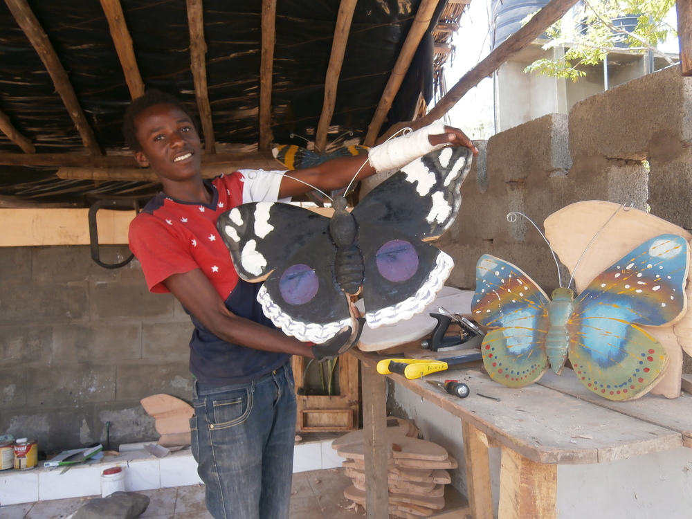 Sadiki still helping to produce a replica butterfly even though he has a broken arm.
