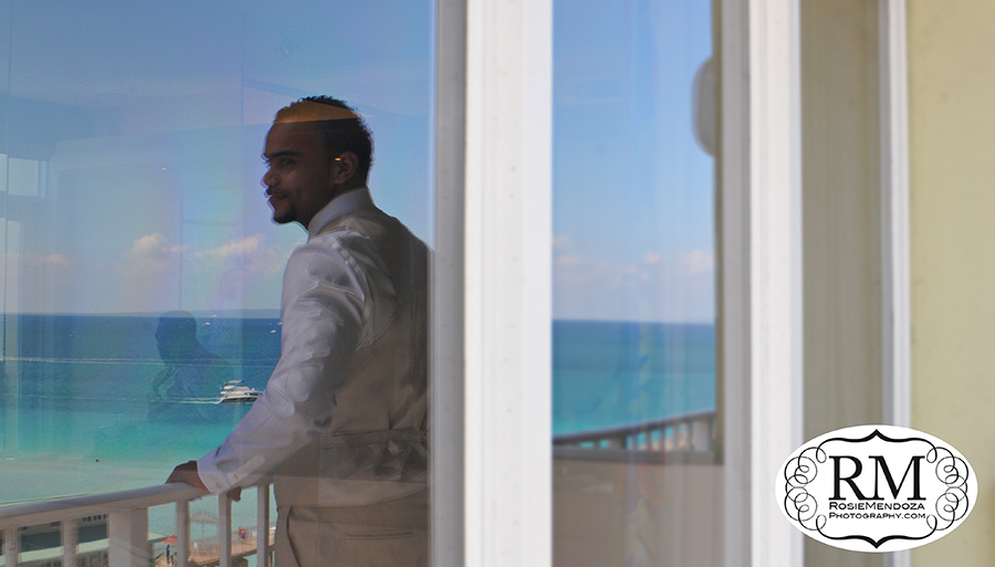 Reflection of the groom looking over Sunny Isles Pier while father of the bride takes care of final wedding details