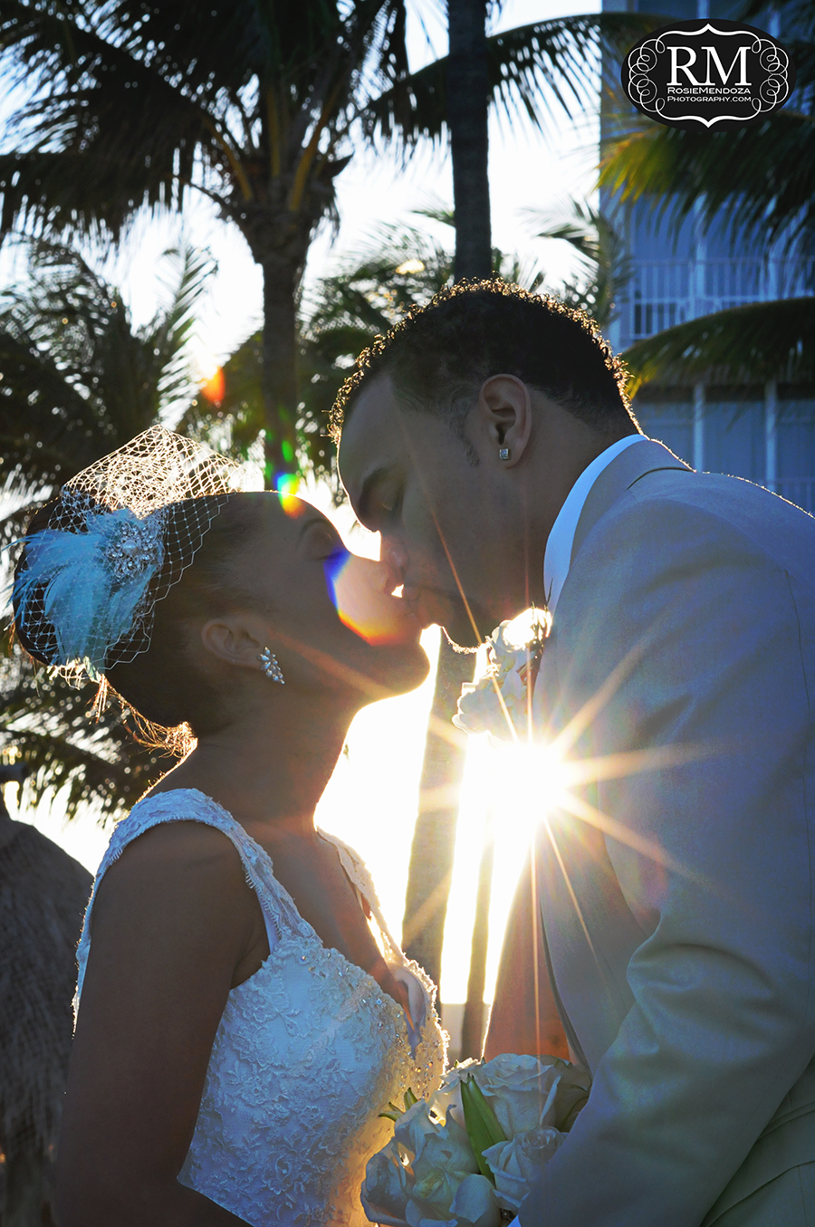 First kiss of wedding couple at sunset by the beach