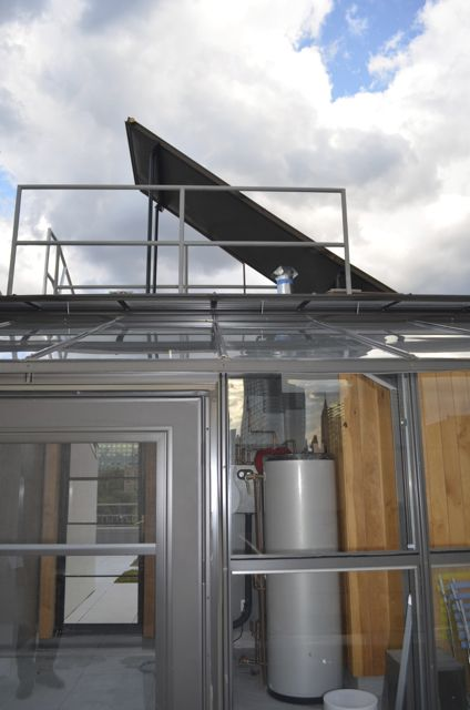 Solar thermal collector on the roof and hot water tank in the greenhouse below