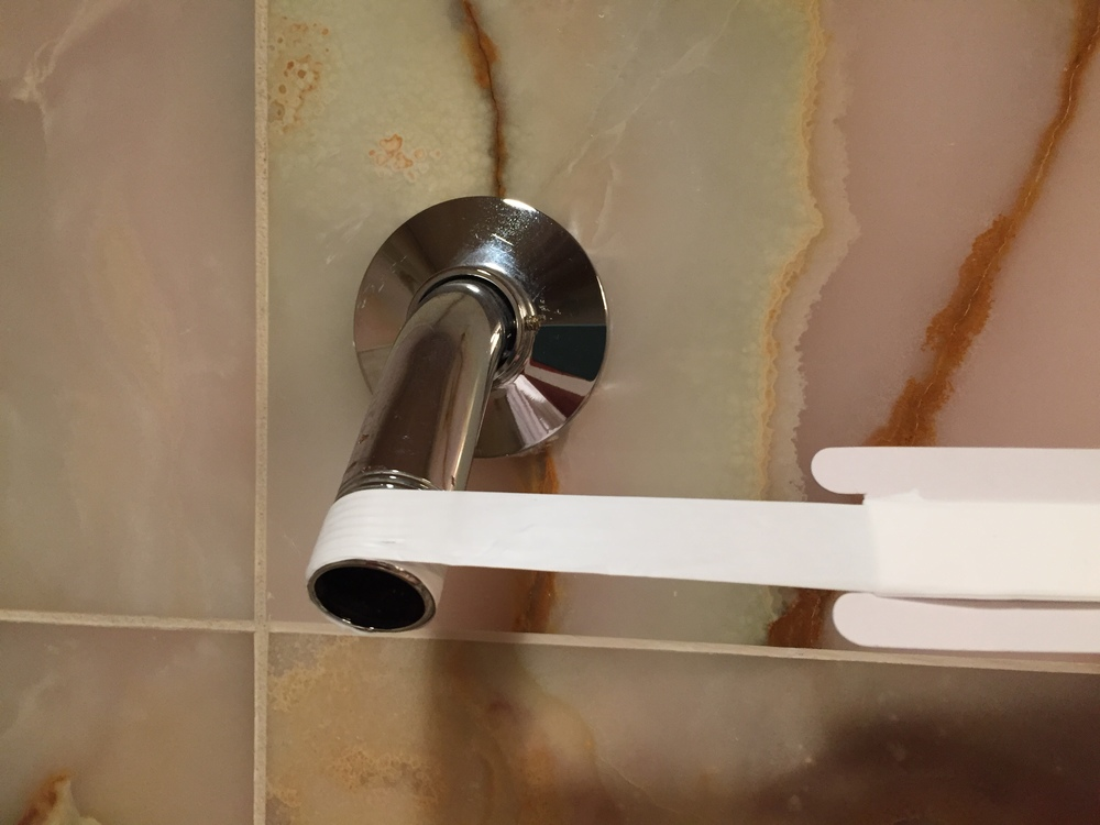 Wrap plumber's tape (thread seal tape) around the shower arm to create a watertight seal