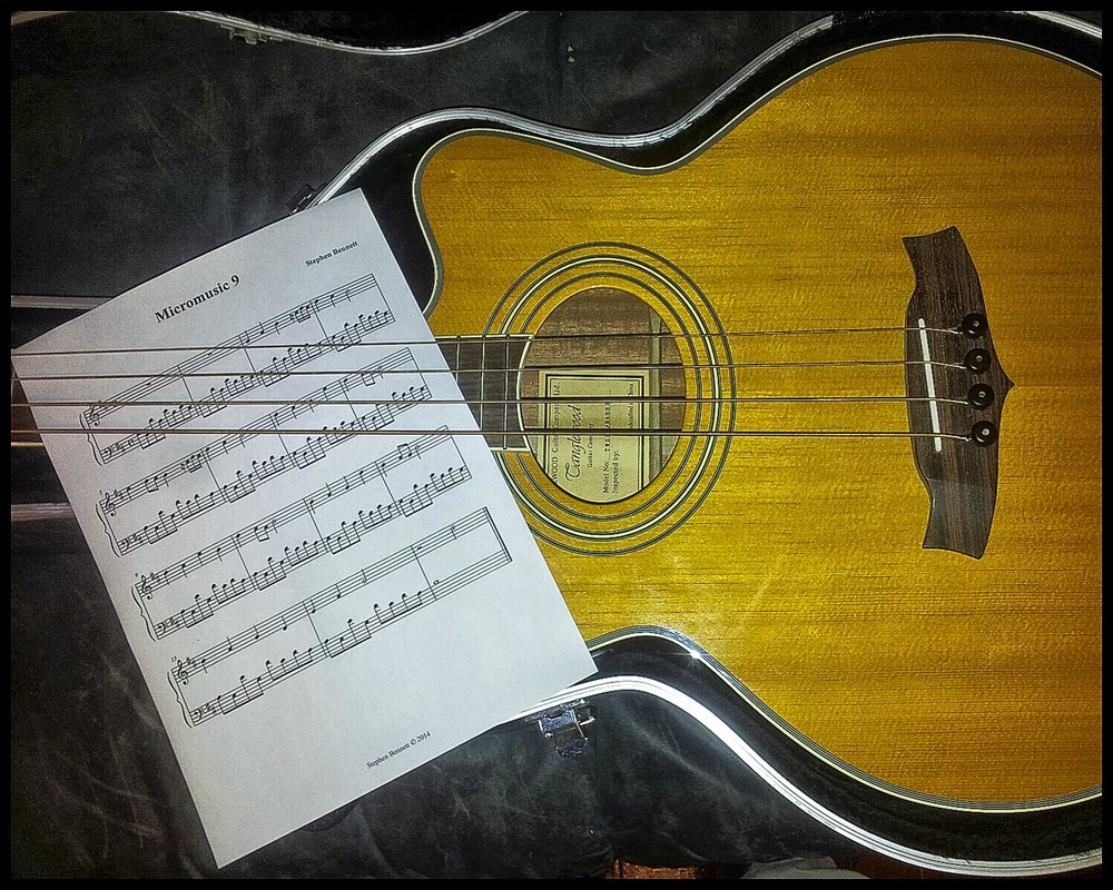 Acoustic bass guitar and music manuscript