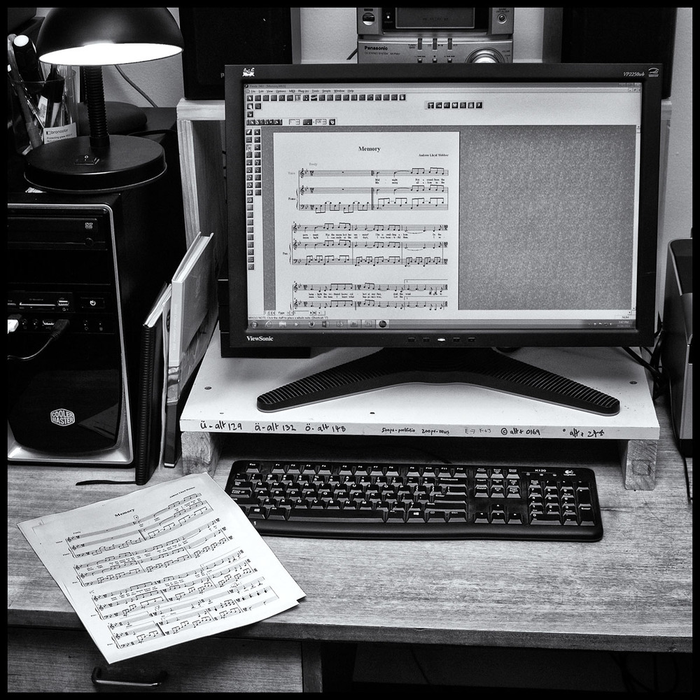 Computer and printout of music manuscript.
