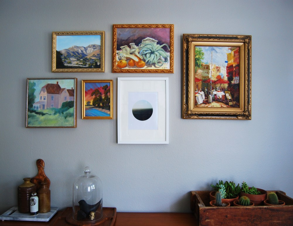 The key to a successful gallery wall is an organic arrangement and similar frames. Here I used a lot of gold hued guilded frames that look nice against the gray wall.