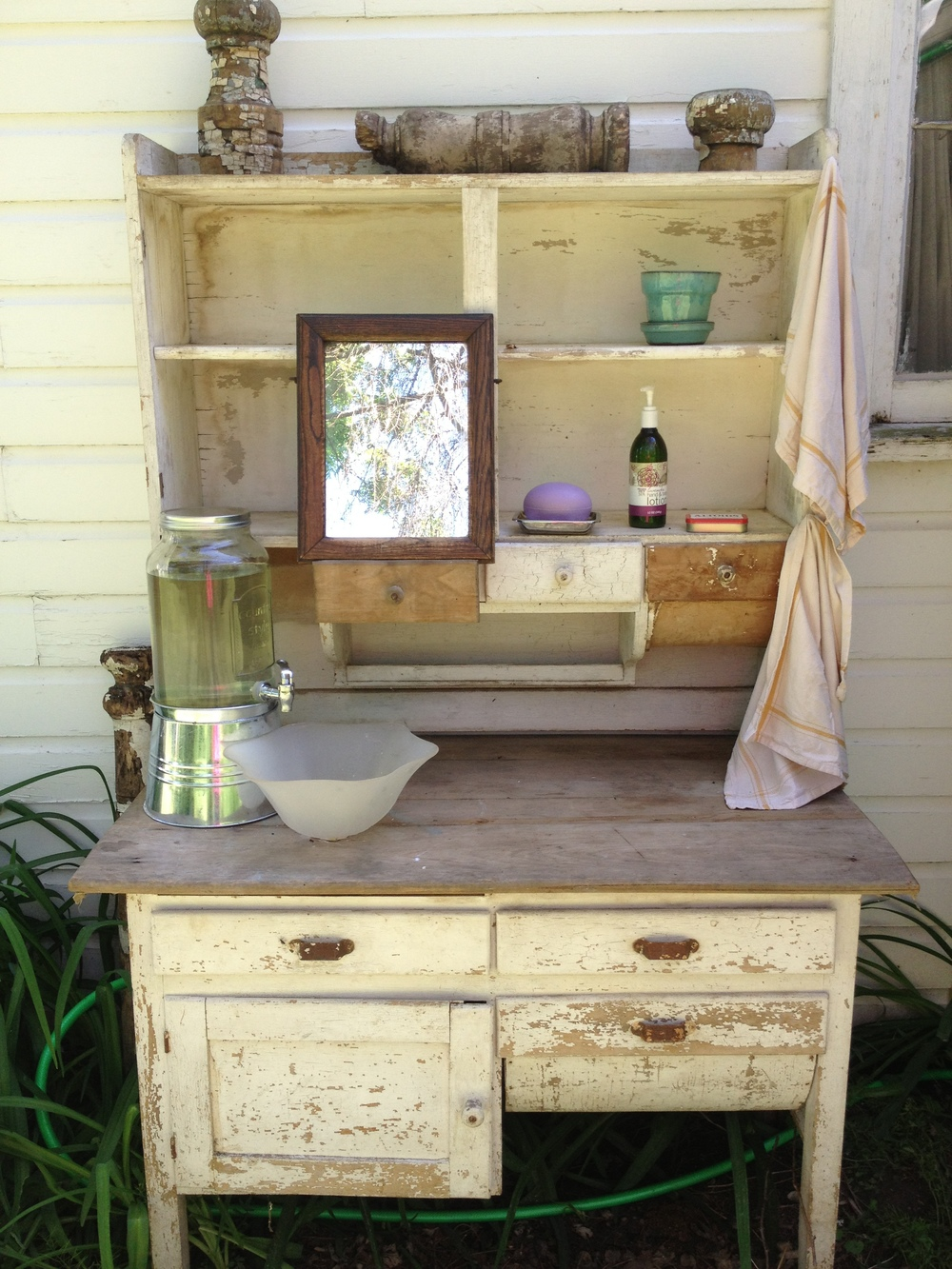 Some guests ended up camping on the property so an antique hutch was outfitted as the washing station next to the port a potties.