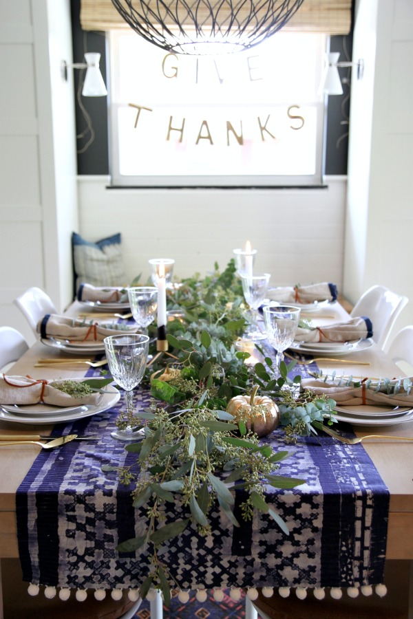 House Tweaking created an exciting table infused with unexpected global vibes Indigo hmong table cloth and napkins create an outrageous backdrop to the gold place settings and natural foliage. Wouldn't this suit a lively Chanukah holiday table as well?