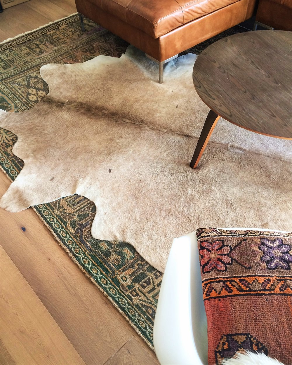 A soft thin natural cowhide over a rougher thin pke rug with blemishes to hide.