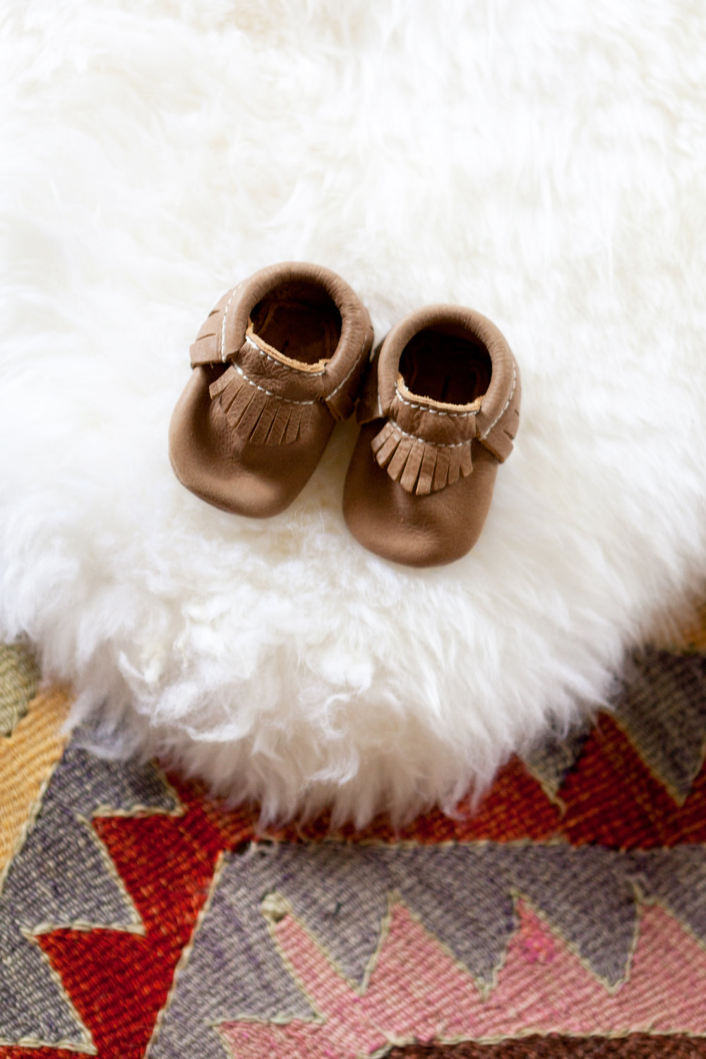 A softer thick sheepskin over a rough thin kilim in a nursery.
