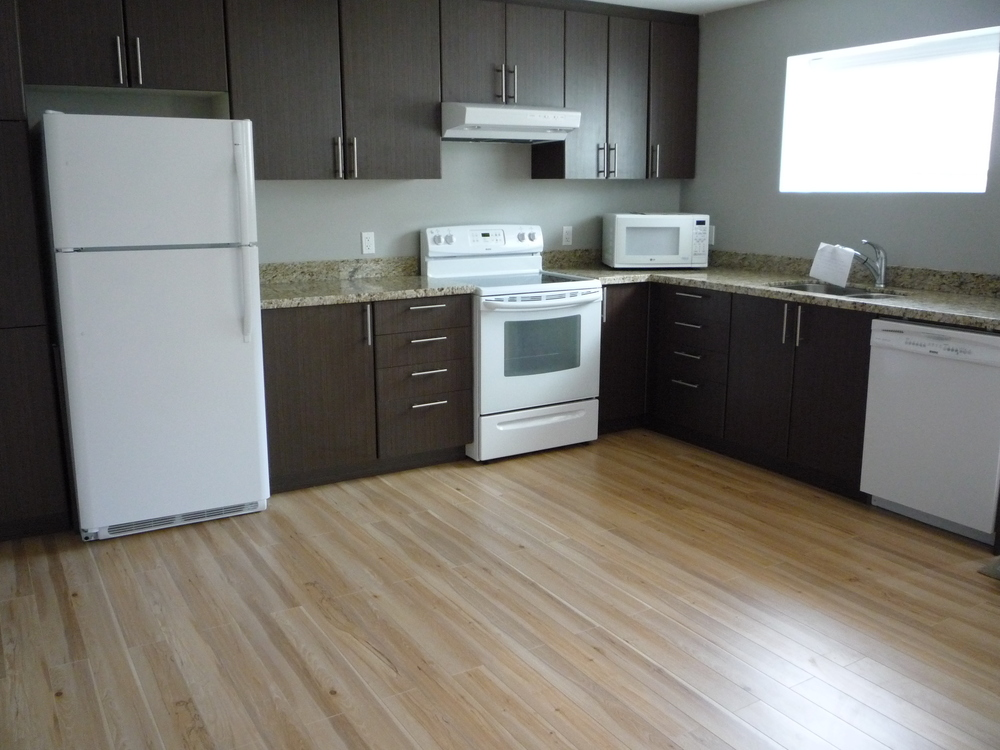 shaped kitchen in legal basement suite with window