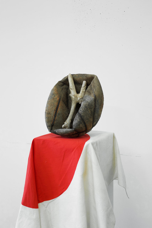 Untitled (red shadow)   2016  Basketball, deer bone, plaster, dirt, and Japanese flag (1950)