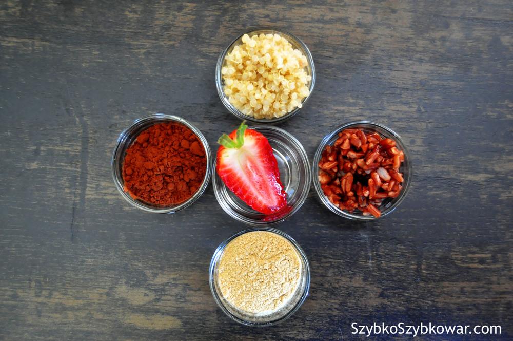 Po lewej - kakao, po prawej - czerwony ryż, u góry - ugotowana quinoa, na dole - proszek z korzenia lukrecji, w środku - truskawka