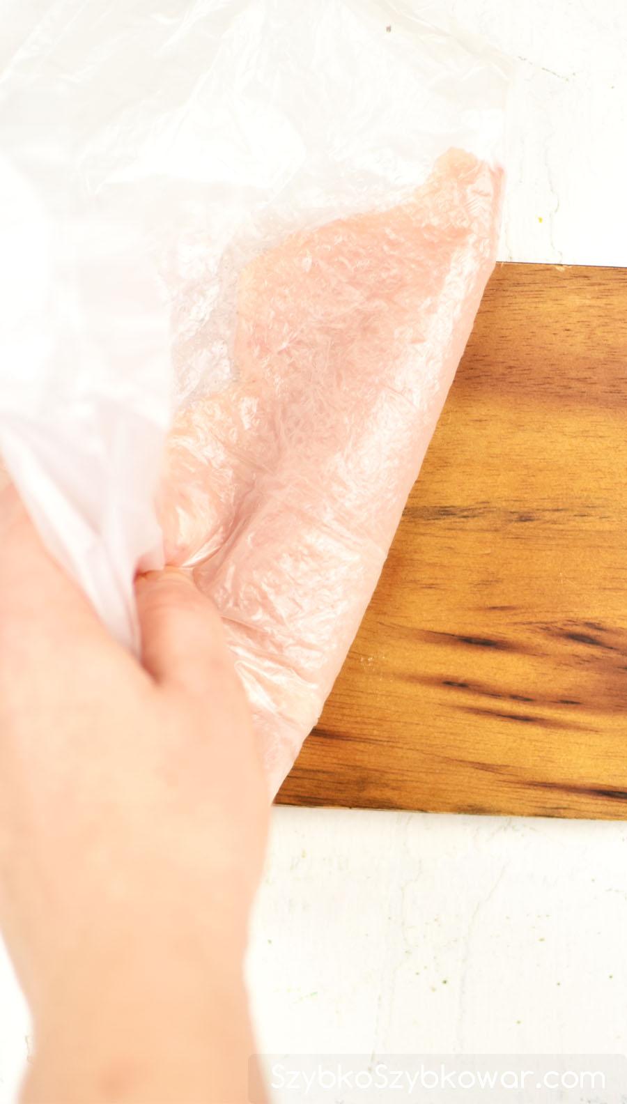 Przykryj ponownie filet drobiowy woreczkiem foliowym, chwyć filet drobiowy z obydwoma woreczkami i odwróć.