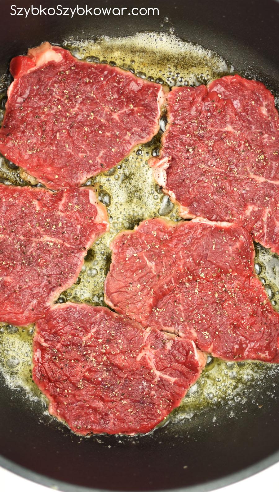 Plastry wołowiny podsmażanie w tłuszczu po cebuli.