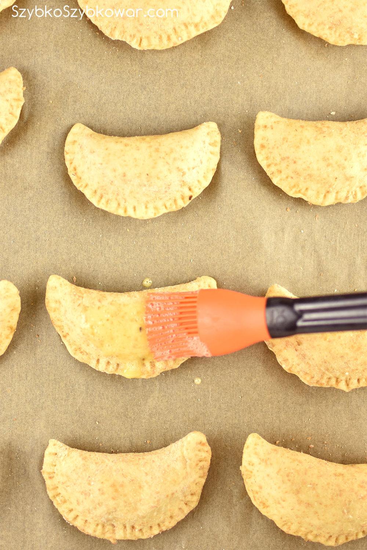 Wyrośnięte pierogi na papierze do pieczenia w czasie smarowania jajkiem.