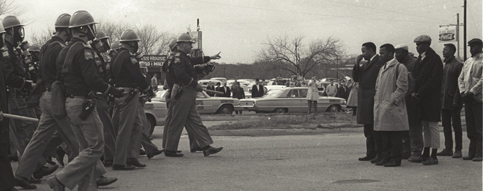 Alabama Highway Patrolmen about to beat down and terrorize young Civil Rights marchers, including John Lewis (in brown raincoat) on Bloody Sunday in Selma, Alabama 1953.