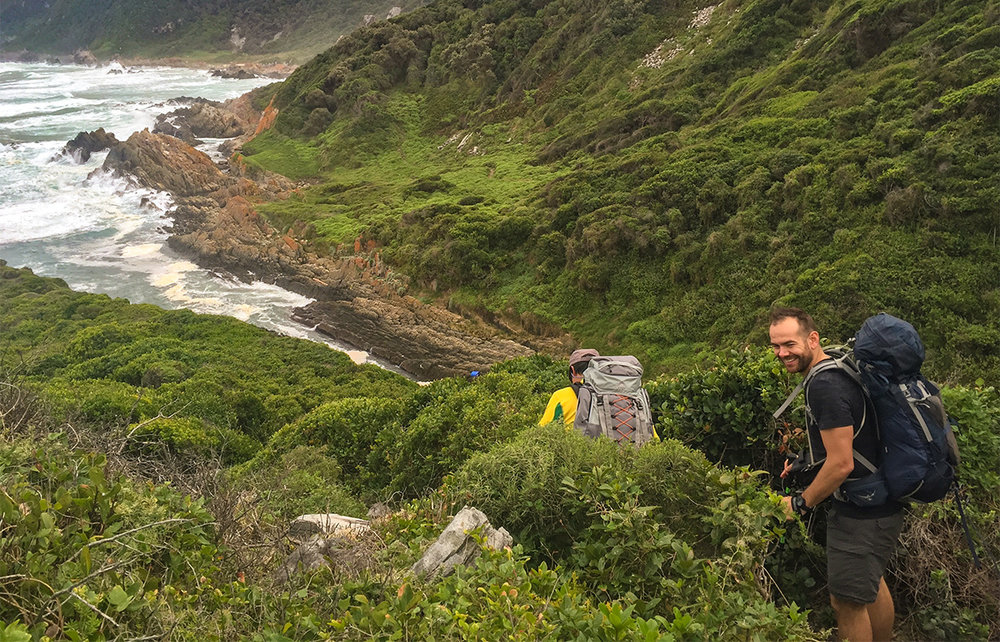 The Otter Trail Day 2 – Most of the trail follows the coastline with thick fynbos on either side. The green fynbos and forest starkly contrasts the orange lichen on the coastal rocks.  Click to expand.