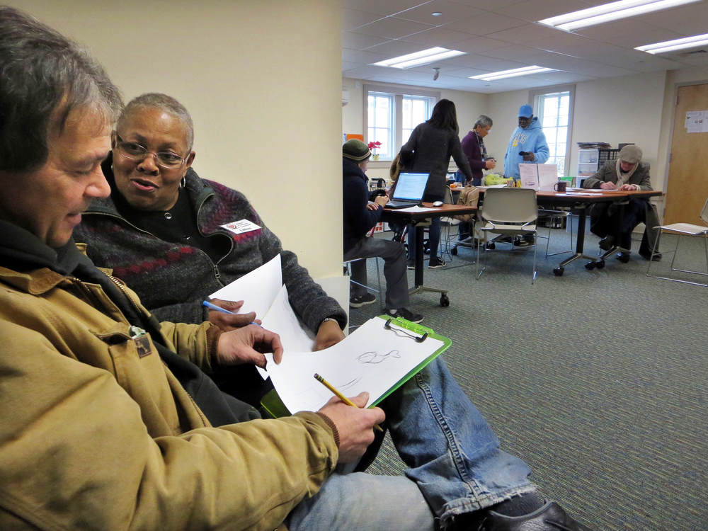 KEVIN GUTTING Artist Art Vicker, left, talks about drawing with Amherst Community Connections staffer Lillian Coleman on Tuesday morning at the drop-in center's new space at the rear of the Unitarian Universalist Society of Amherst. In background, executive director Hwei-Ling Greeney, standing center, helps other visitors use the resources at the center.   Photo courtesy of The Amherst Bulletin Website. ACC does not own the rights to this image.