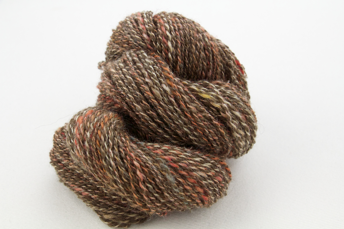Handspun yarn.  One ply is from a batt containing Bluefaced Leicester Wool, Tussah Silk, brown Merino Wool, red Kid Mohair, Angelina, and more.  The other ply is natural colored Shetland blended with cinnamon and white Alpaca.