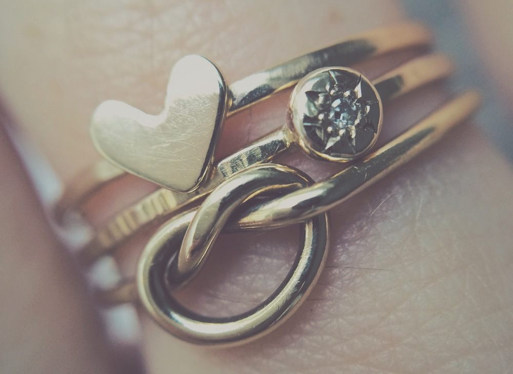 heart stacker, compass rose diamond ring, and knot ring in yellow gold
