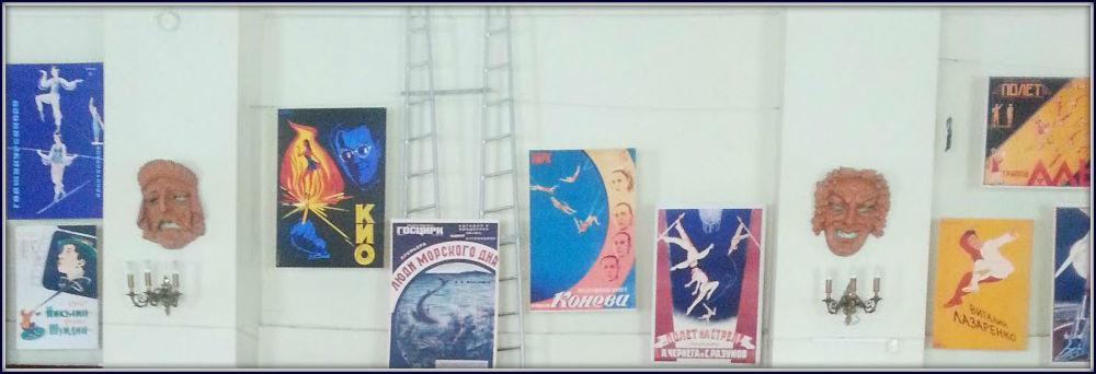 Afiches, máscaras, candelabros y escaleras originales en la sala de exhibición.