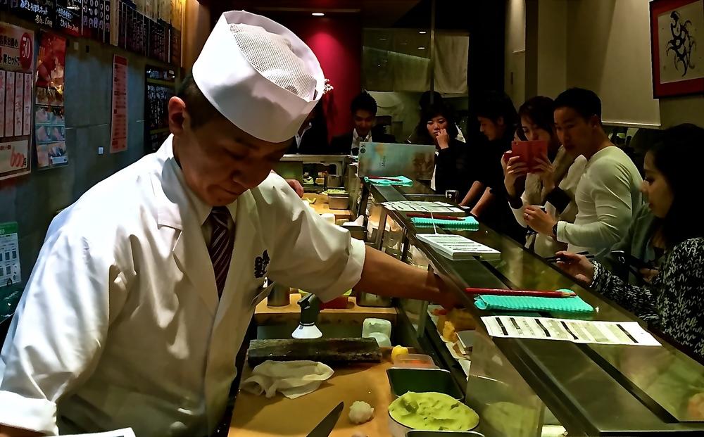 """Master del sushi.Una barra en forma de """"ele"""", tres cocineros y ninguna silla. El local se llenay la gente de afuera asoma las cabezas ante el menor movimiento y a la esperanza de un hueco.Las piezas salen en números pares y se ordenan en la medida en que se van consumiendo. Tokyo, Japón - Abril 2015"""
