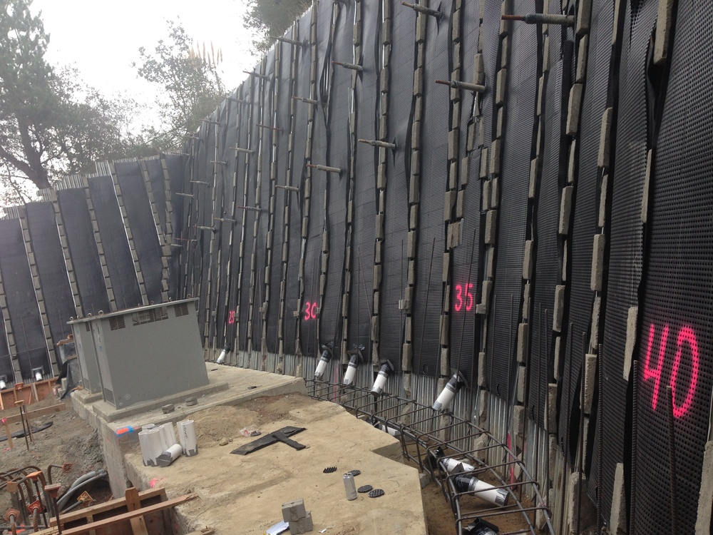 The soil nails and black drainage mats shown here are part of the Criblock retaining wall at the standby power building.Criblock is a reinforced concrete wall system using the mass of concrete for structural stability.