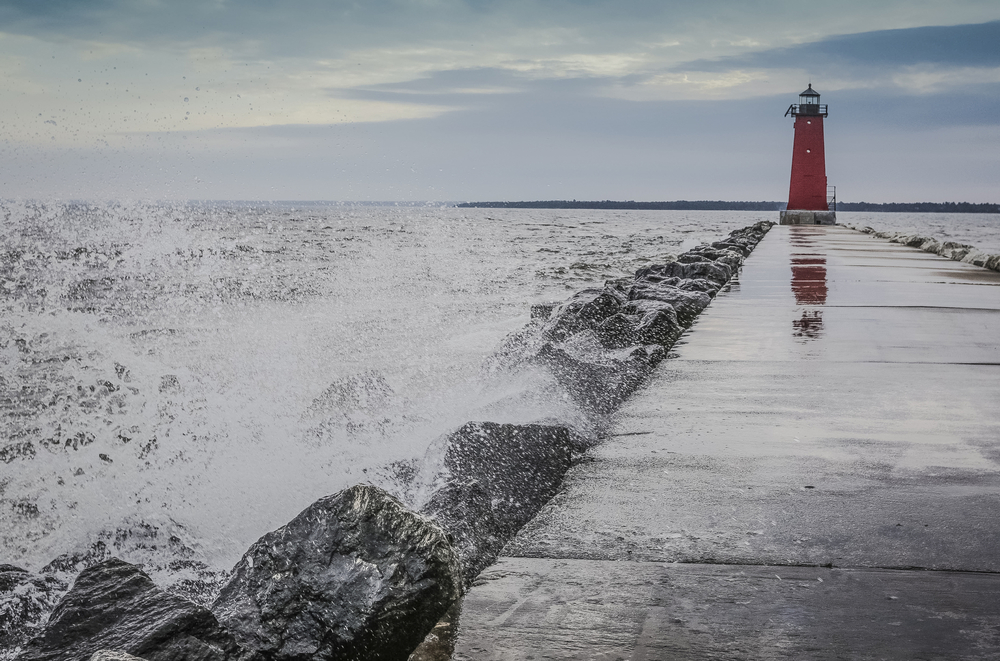Waves crash along the Manistique East Breakwater Lighthouse at the Lake Michigan Beach in Manistique, MI in Michigan's Upper Peninsula. Ryan Garza / Pop Mod Photo
