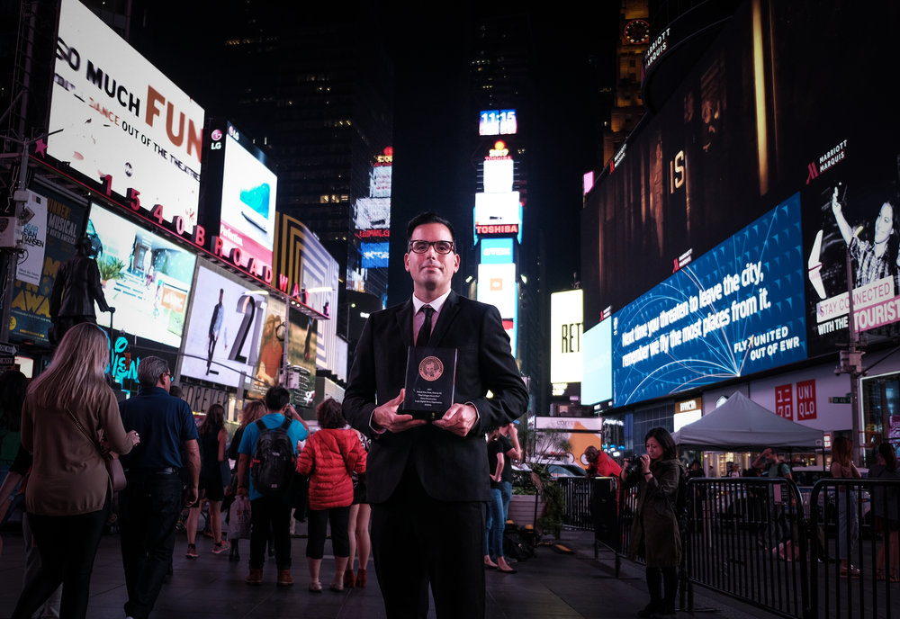 Pop Mod Photo co-owner Ryan Garza poses for a photo in Times Square with his Edward R. Murrow award following the Edward R. Murrow Awards Gala in New York City. Garza's work on the Flint Water Crisis for the Detroit Free Press with co-worker Brian Kaufman was awarded for New Documentary for Large Digital News Organization.