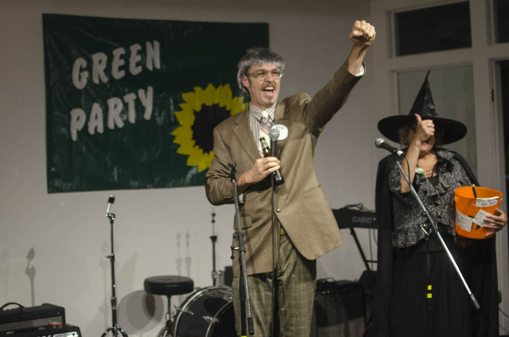 Kevin Bott, clad in a festive wig and costume, roots for the Green Party as an introduction to his short speech at the Green Party Halloween Party Sunday evening.