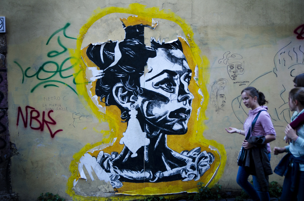 Street art, a prevalent societal stamp on Rome, is displayed in an alleyway as a group of girls strolls through.