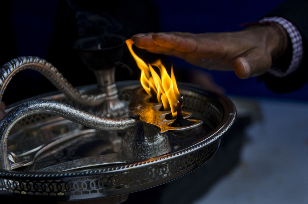 As community members exit the temple at Bhaktivedanta Manor after praying to the gods, they lay their hands close to this flame and say a prayer at the annual Diwali festival.