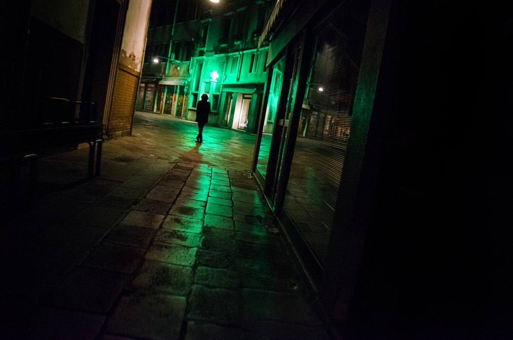 A young woman strolls alone through the streets of Venice on a brisk autumn night.