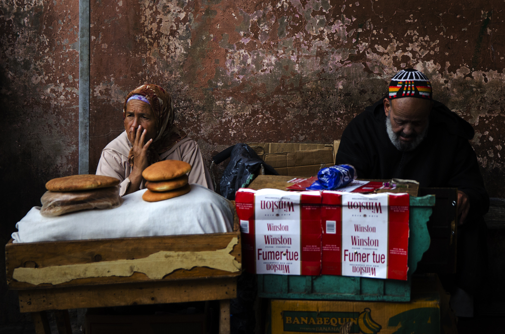 A woman selling traditional Moroccan bread sits beside a man selling cigarettes in the Souks of Marrakech. Both are typical goods to be purchased in the marketplace and around the city.