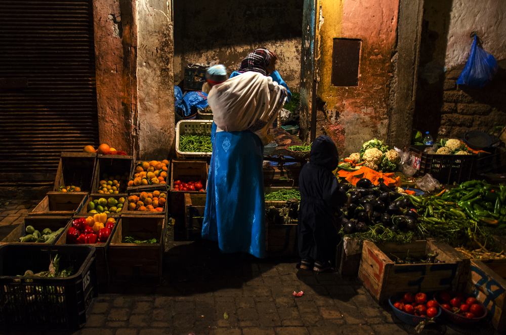 A woman and her two children shop in the Souks of Marrakech, Morocco for vegetables and fruits one November evening.