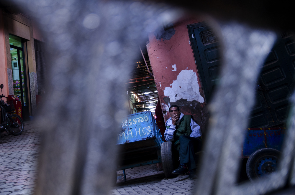 A man sits outside his stall in the Souks of Marrakech on a warm November afternoon.