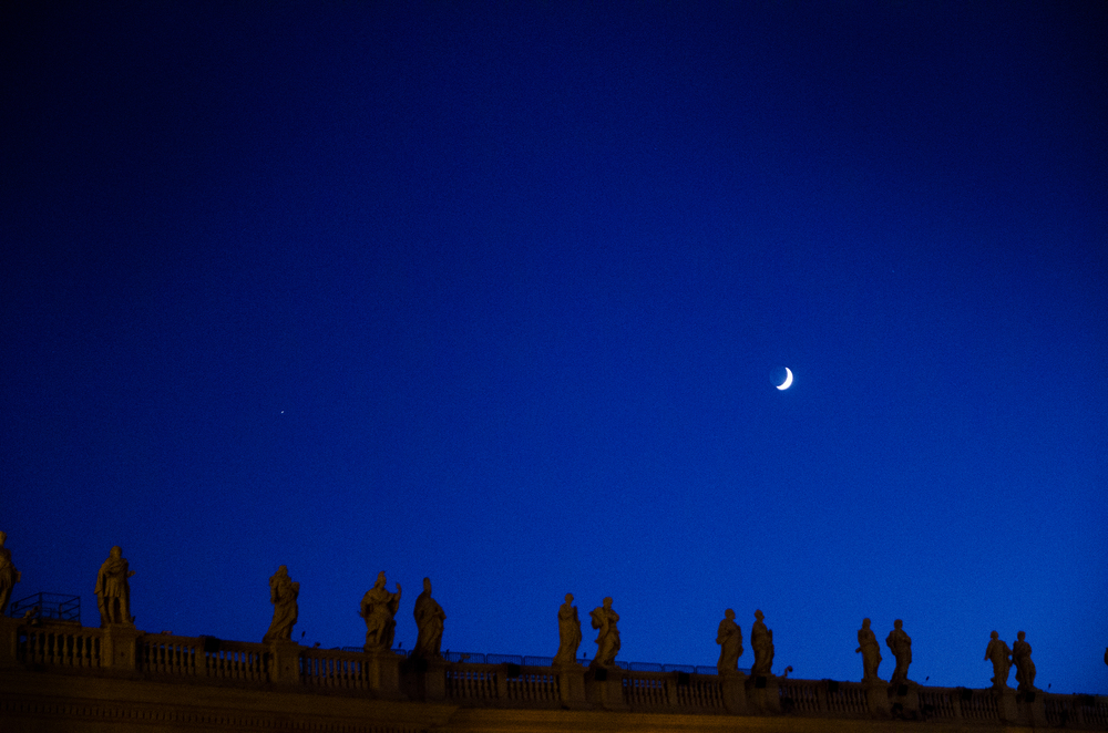 Overlooking the Main Square outside of St. Peter's Basilica, these statues stand tall silhouetted by a crescent moon in Vatican City, Italy.