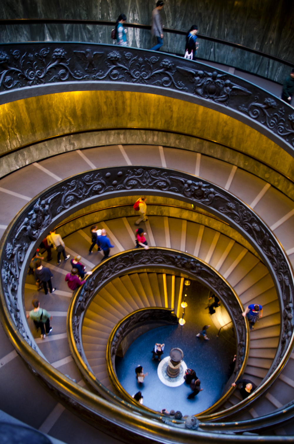 This winding path leads to the exit of the Vatican Museums, spiraling downwards on a shallow slope, causing patrons to tread carefully on the steps.