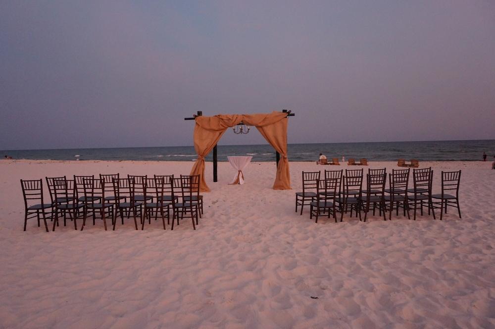 White beach wedding with burlap and dark bamboo arbor