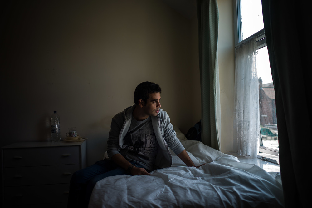 Ahmad Marcos, sitting in his new bedroom in Middlesborough, having spent 55 days on the road from Aleppo, Syria.  Middlesborough, England  July 2015