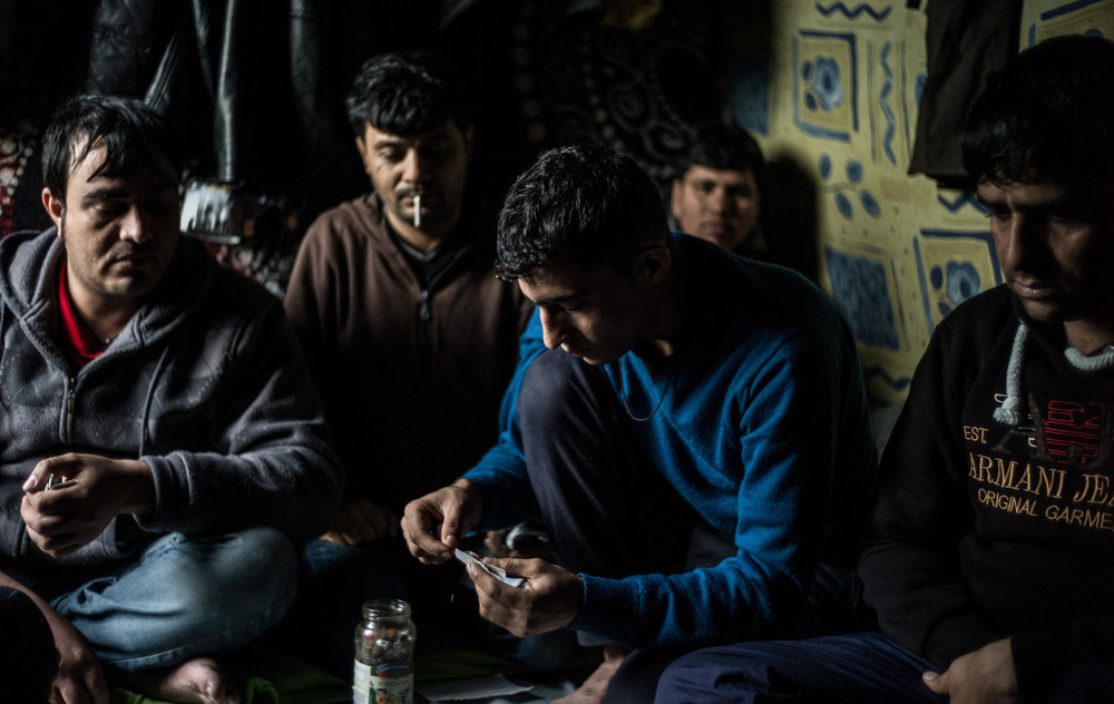 Five men from Afghanistan sitting in the Calais refugee camp in Northern France. All of these men used to work for The International Security Assistance Force (ISAF) a NATO-led security mission in Afghanistan.   Calais, France.   January 2016