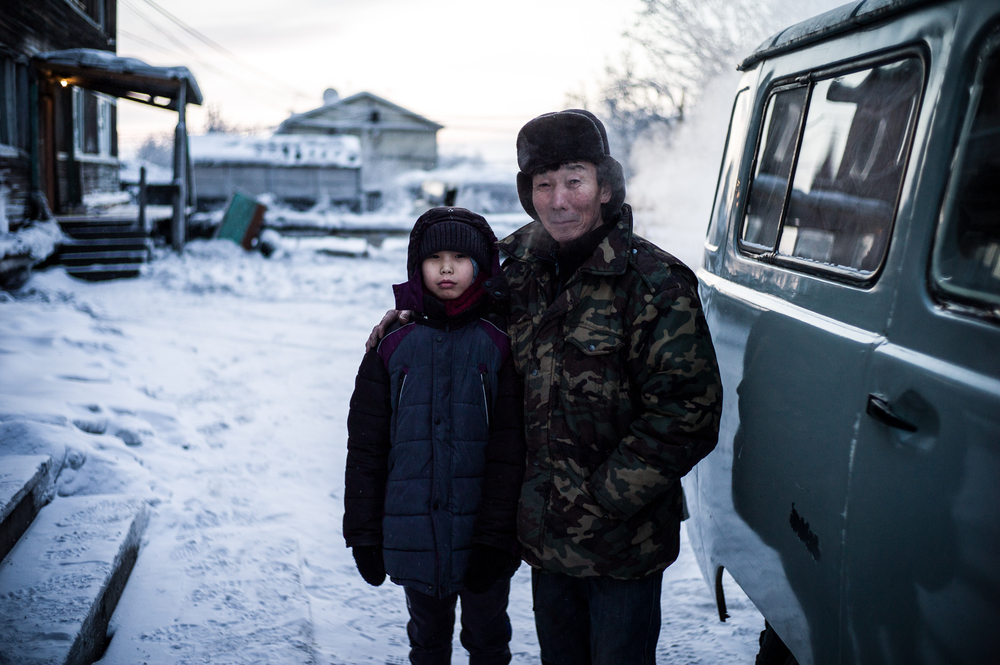 A Grandfather and his Grandson outside their home in Khandyga, the siberian province of Yakutia.   Siberia, Russia.   January 2016
