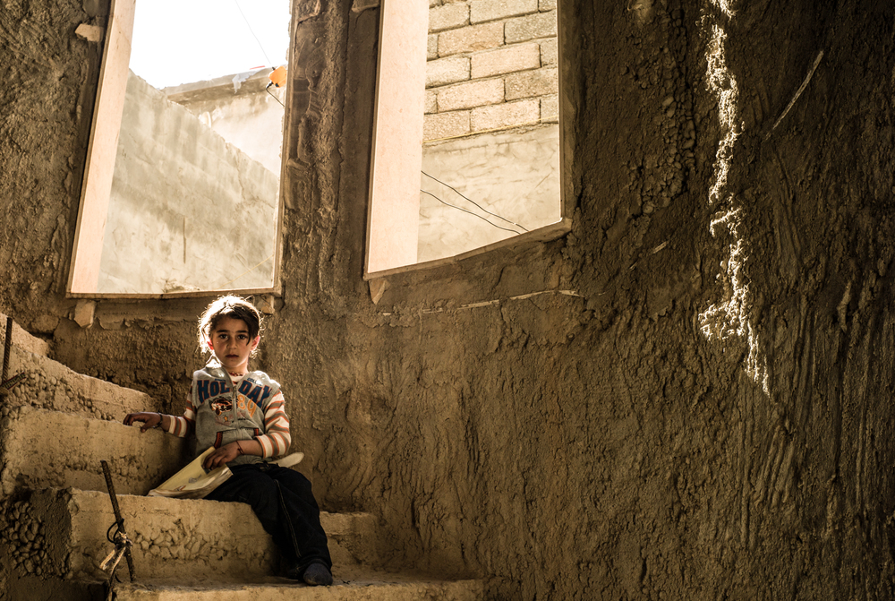 The daughter of a Yazidi Peshmerga fighter sits on the stairs of an unfinished concrete building.  Khanke, Northern Iraq  February 2016