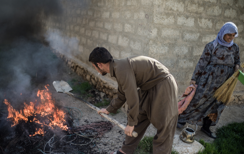 A man and woman burn the plastic off wires gathered in coalition air strike wreckage, in order to sell at a nearby market.  Sinjar, Iraq  21st FEB 2016